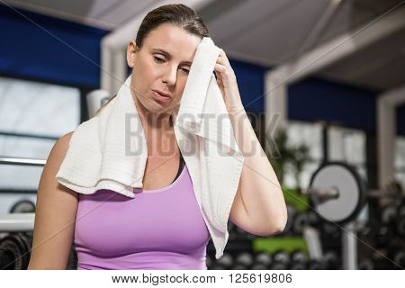 Woman wiping sweat with towel at the gym