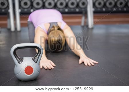 Determined woman stretching at the gym