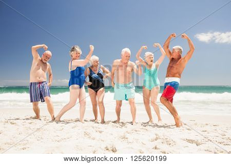 Senior friends showing their muscles on the beach