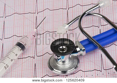 Close up of a Electrocardiograph also known as a EKG or ECG graph with a stethoscope and syringe