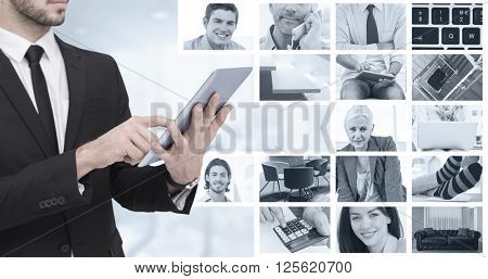 Mid section of a businessman using digital tablet pc against composite image of businessmen using laptop