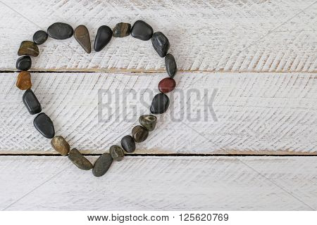 Heart shaped dark shades of stone, small pebbles arranged as a heart on white wooden background
