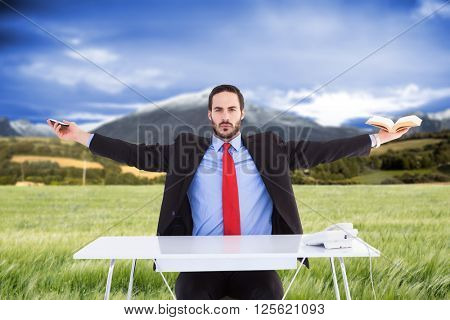 Unsmiling businessman sitting with arms outstretched against scenic backdrop