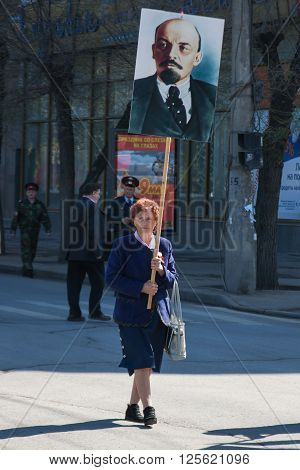 Volgograd, Russia - May 1 2011:Woman with portrait of the Soviet founder Vladimir Lenin takes part in the May day demonstration in Volgograd