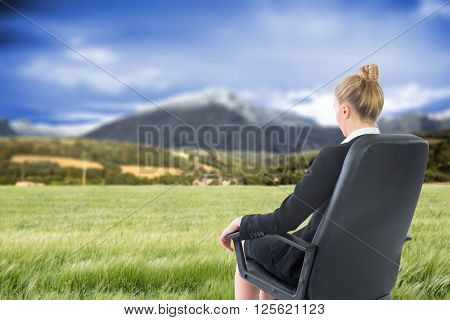 Businesswoman sitting on swivel chair in black suit against scenic backdrop