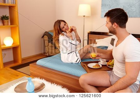 Happy young couple having breakfast in bed, enjoying themselves.