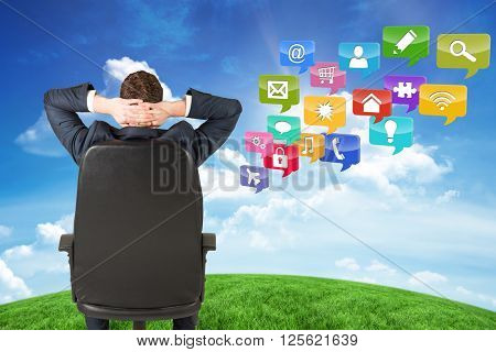 Businessman sitting in swivel chair against green hill under blue sky