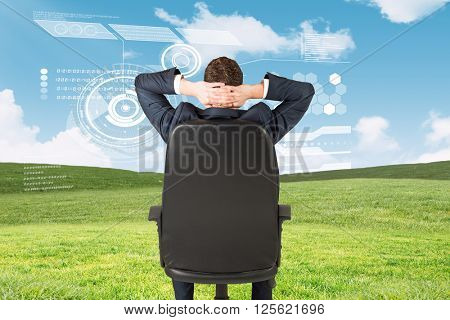 Businessman sitting in swivel chair against blue sky over green field