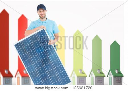Smiling construction worker holding solar panel against seven 3d houses representing energy efficiency