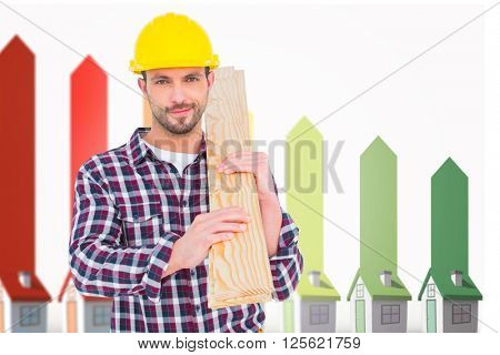 Handyman holding wood planks against seven 3d houses representing energy efficiency