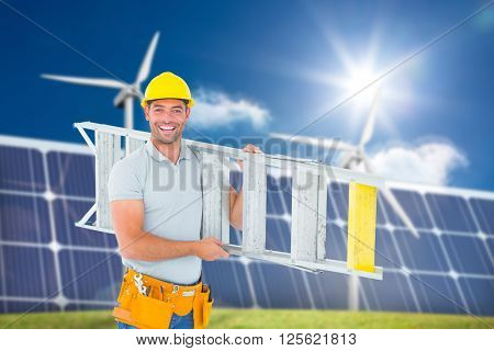 Portrait of smiling repairman carrying ladder against wind turbines and solar panels