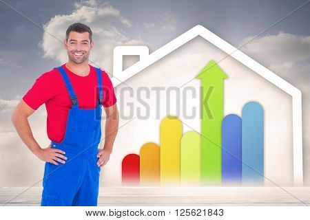 Happy handyman in overalls with hands on hip against diagram of a house with energy rating chart
