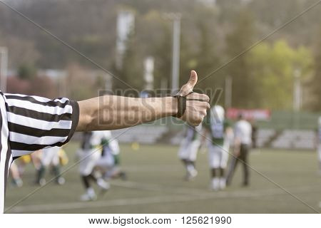 Hand of football referee showing signal with his thumb up