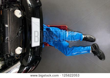 Mechanic In Blue Uniform Lying Down And Working Under Car At The Garage