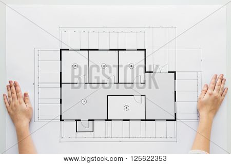 business, architecture, building, construction and people concept - close up of hands with architectural blueprint