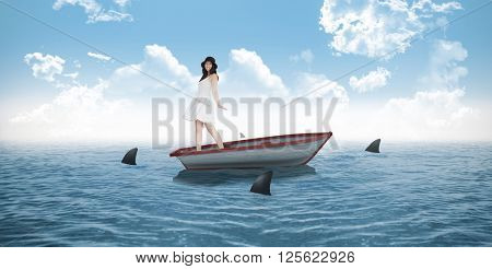Woman twirling in her pretty dress against sharks circling small boat in the ocean