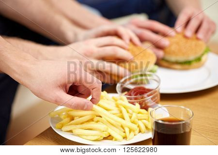 fast food, unhealthy eating, people and junk-food - close up of male hands with french fries and hamburgers on table at home