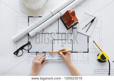 business, architecture, building, construction and people concept - close up of architect hands with ruler and pencil measuring living house blueprint