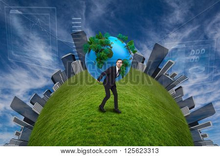 Businessman carrying the world against view of the blue sky