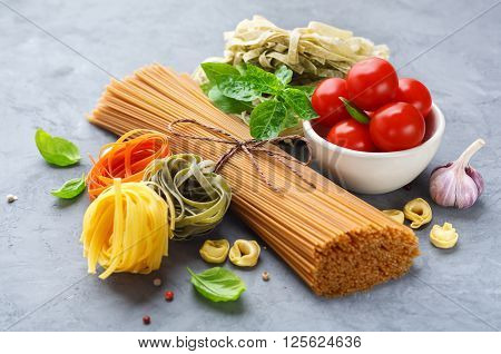 Dry pasta with tomato Spaghetti tortellini and tagliatelle garlic and basil. Italian cuisine