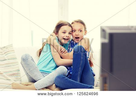 people, children, television, friends and friendship concept - two scared little girls watching horror on tv at home