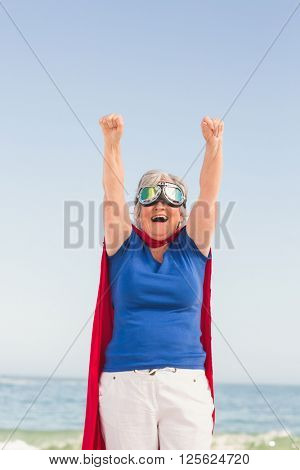 Senior woman pretending to be a superhero on a sunny day