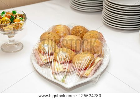 Sandwiches on a silver tray covered with transparent foil