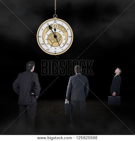Businessman carrying briefcase against hanging pocketwatch