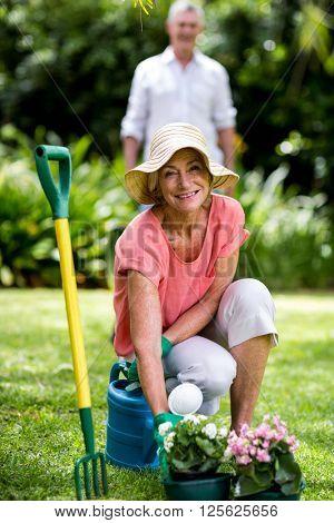 Senior woman with gardening equipment against man in yard