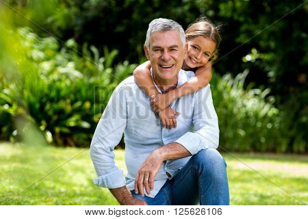Happy grandfather and grandaughter smiling at yard