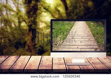 Computer screen against wooden walkway along grassland
