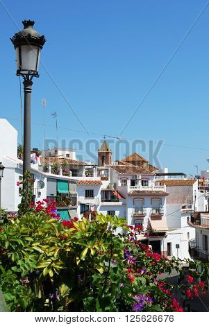 View along the main shopping street with the church to the rear Torrox Malaga Province Andalucia Spain Western Europe.
