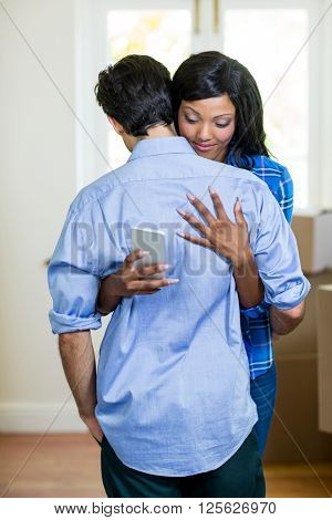 Woman checking her mobile phone while embracing a man at home