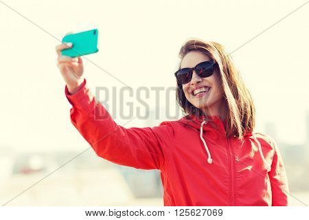 lifestyle, leisure, technology and people concept - smiling young woman or teenage girl in sunglasses taking selfie with smartphone outdoors