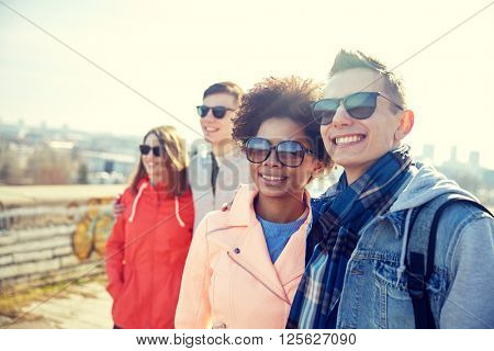 tourism, travel, people, leisure and teenage concept - group of smiling teenagers in sunglasses hugging on city street