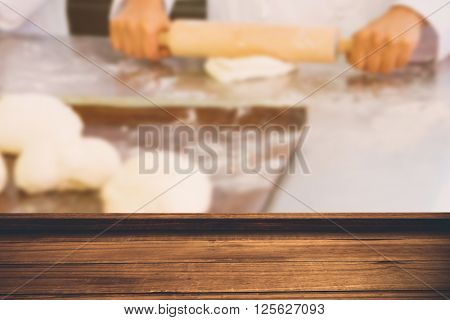 High angle view of wooden flooring against baker kneading dough with rolling pin