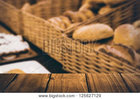 Wooden table against close up of basket with fresh bread and pastry Close up of basket with fresh bread and pastry at the bakery