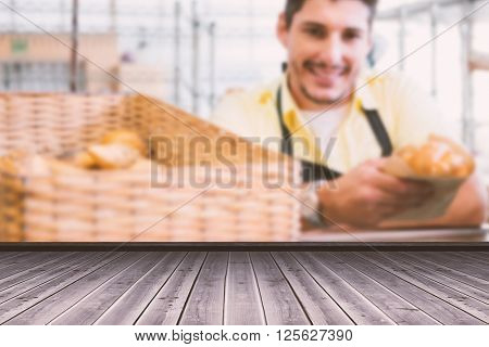 High angle view of gray hardwood floor against smiling server in apron holding bread