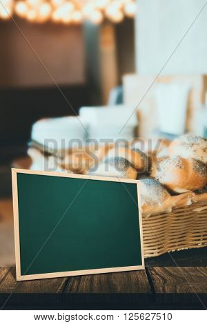 chalkboard against basket with fresh and delicious roll of bread