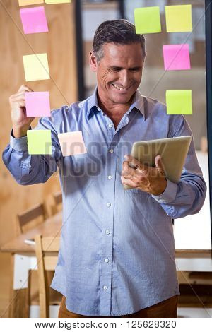 Man using digital tablet while writing on sticky notes in office