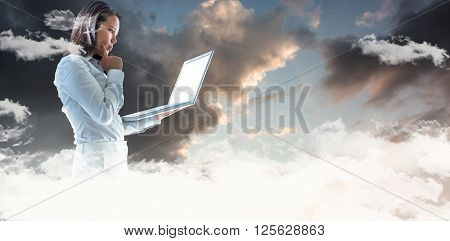 Businesswoman with finger on cheek using laptop against blue and orange sky with clouds