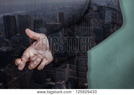 Businessman with fingers crossed against blue background