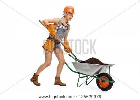 Female construction worker unloading a wheelbarrow full of dirt with a shovel isolated on white background