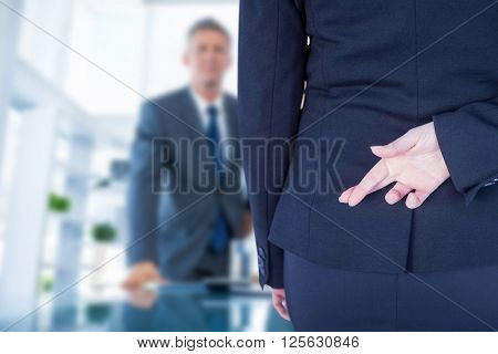 Businesswoman with fingers crossed behind her back against business people looking at camera behind desk