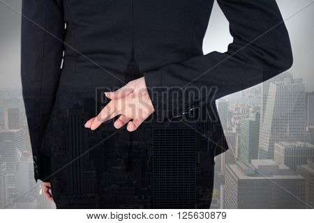 Businesswoman with fingers crossed behind her back against city skyline