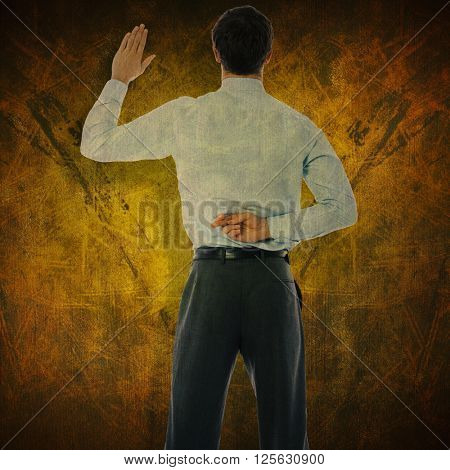 Businessman crossing fingers behind his back against dark background