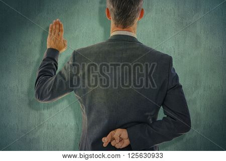 Rear view of businessman taking oath with fingers crossed against blue background
