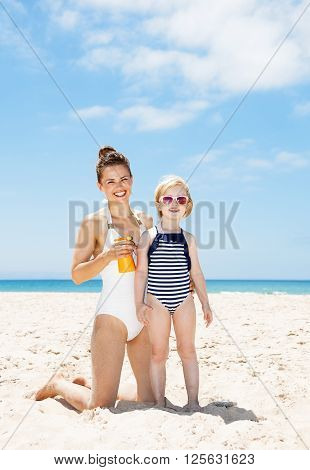 Happy Mother Applying Sunscreen On Child In Swimsuit At Beach