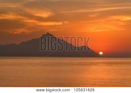 Beautiful sunrise on Greek coast of Aegean sea with holy mountain Athos. Chalkidiki Greece. ** Note: Visible grain at 100%, best at smaller sizes