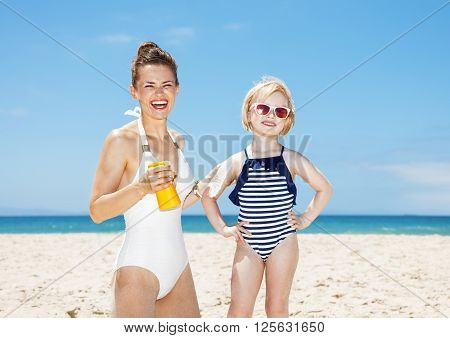 Smiling Mother Applying Sunscreen On Daughter's Arm At Beach